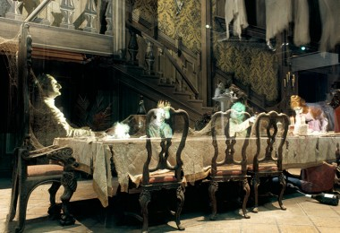 photo of Haunted Mansion Dining Room in Disneyland attraction showing ghostly apparitions seated at long formal dining table in a great hall