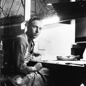 black and white photo of a young Walt Disney at workbench wearing a full-length apron