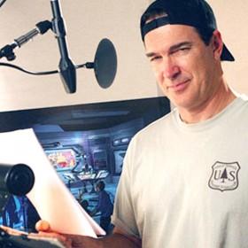 photo of Patrick Warburton in recording studio behind microphone holding script