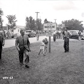 photo of Walt Disney walking across grass beside city limits sign for Marceline Missouri in 1956