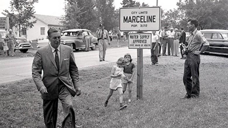 photo of Walt Disney walking across grass beside city limits sign for Marceline Missouri in 1956