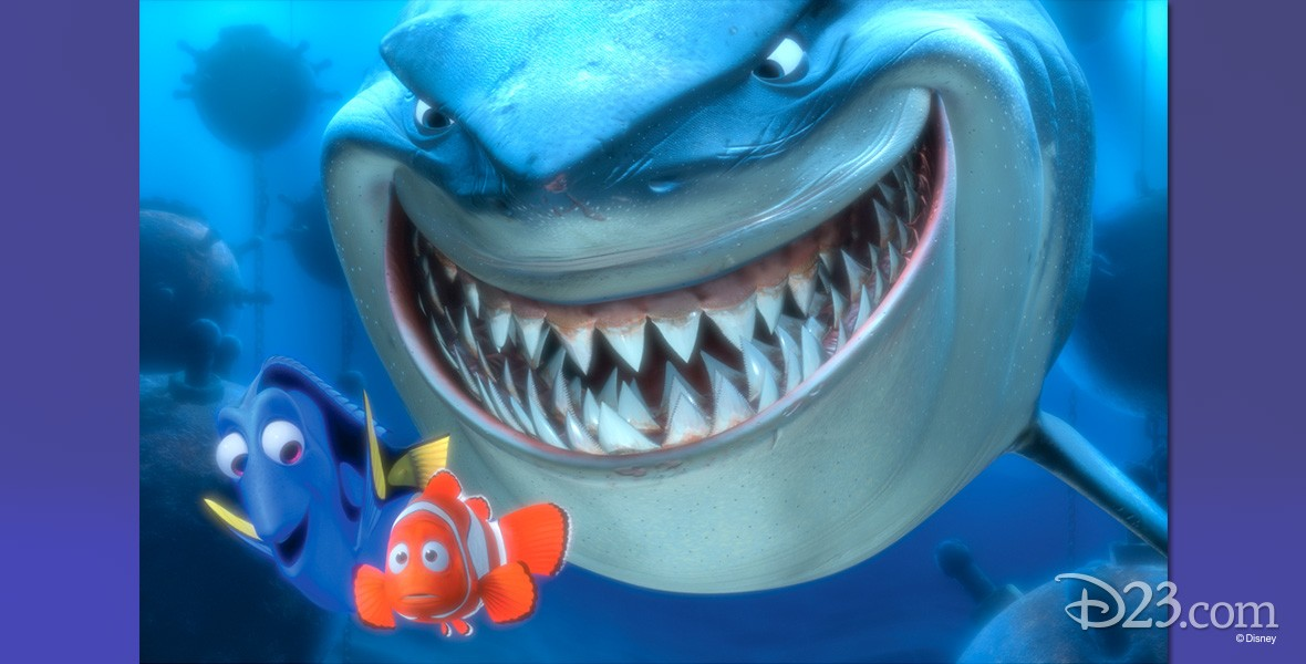 animation still from the feature Finding Nemo showing a giant grinning shark looming behind the minuscule Nemo