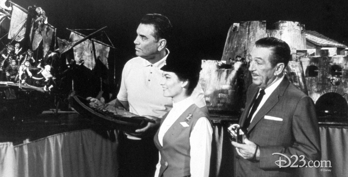 Walt Disney standing with Imagineers
