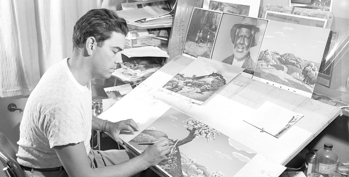 Claude Coats at his desk painting