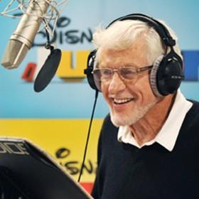 photo of Dick Van Dyke in recording booth wearing headphones