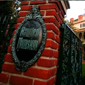 photo of entrance gate and bronze sign for Haunted Mansion at Disneyland