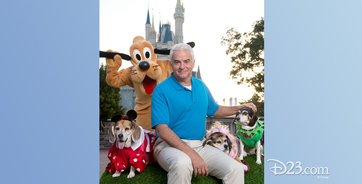 photo of host seated with Goofy character and two dogs in costume from America's Cutest: Disney Side Howl-0-Ween