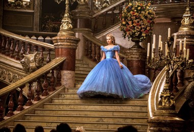 movie still of Cinderella in an elaborate blue dress descending grand stairway