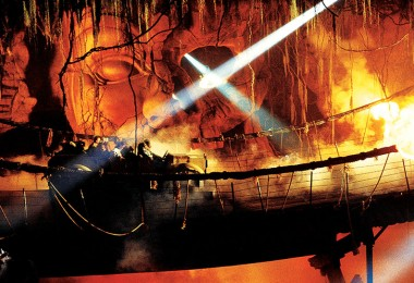 photo of guests in ride vehicle on wobbly rope bridge passing through fire in underground cavern on Indiana Jones Adventure at Disneyland Resort