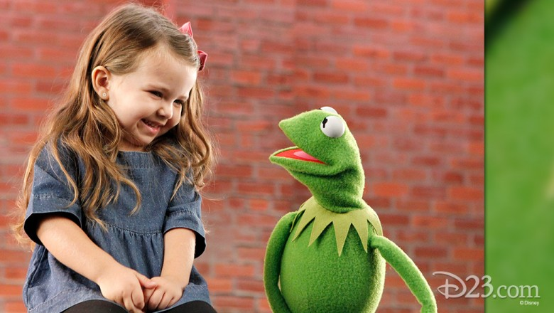still of little girl laughing as she talks to Kermit the Frog