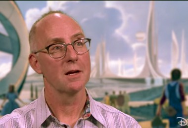 photo of art director Ramsey Avery in front of illustration of Tomorrowland from the movie Tomorrowland