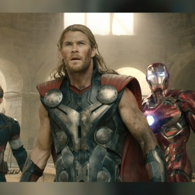 still from the movie The Avengers showing all superheroes assembled in a line inside massive hall