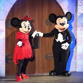 Minnie Mouse and Mickey Mouse at castle double doors each with a hand grasping a door handle ready to pull them open