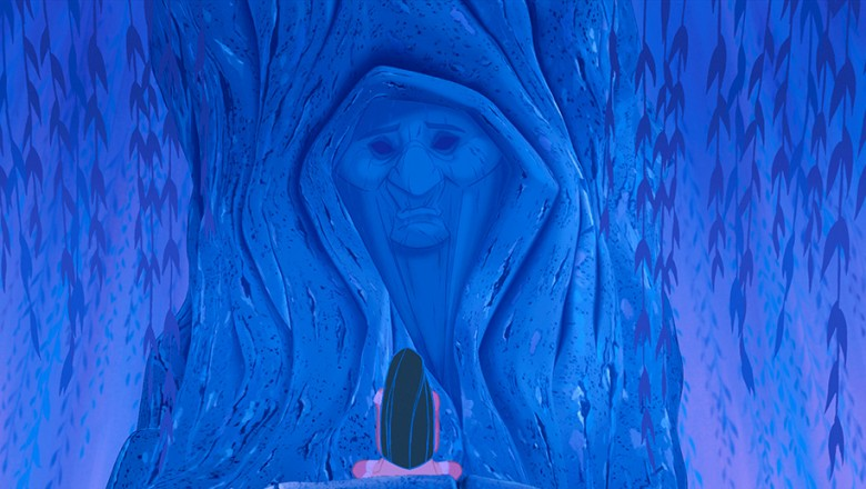 frame from animated feature Pocahontas showing eponymous character seated before a huge face appearing the wall of a cave