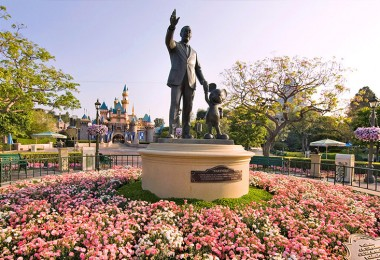 photo of statue of Walt Disney holding hands with Mickey Mouse at Disneyland, placard reading Partners, surrounded by large circular flower bed with Seeping Beauty Castle in background
