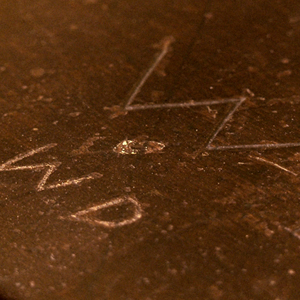 close up photo of Walt Disney's initials scratched into his childhood school desk from Marceline, Missouri