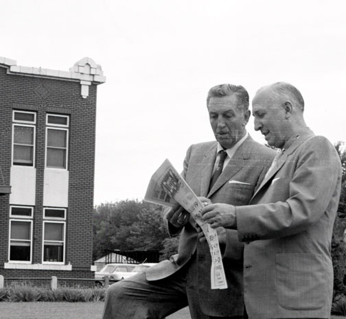photo of Walt and Roy Disney on street reading local newspaper in Marceline, Missouri