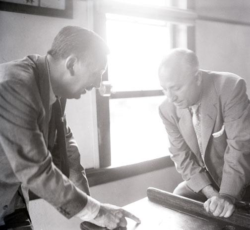 photo of Walt and Roy Disney looking at Walt's childhood school desk