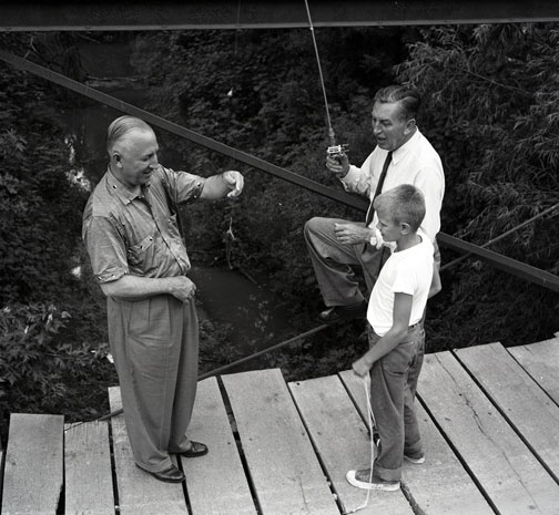 photo of Roy and Walt Disney fishing from a bridge over a creek with a small boy