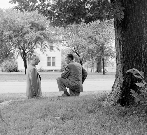 photo of Roy and Walt under a large cottonwood tree, foreground, a two-story white farmhouse in background