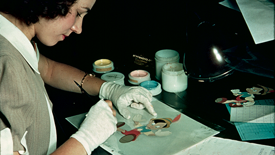 An artist in the Inking and Painting Department adds color to a cel featuring Pinocchio