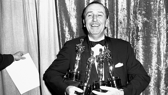 photo of a beaming Walt Disney holding four Oscar(R)s to his chest