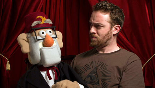 photo of Gravity Falls creator and executive producer Alex Hirsch with life-size Grunkle Stan character
