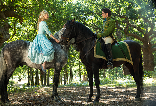 "still from the movie Cinderella featuring Lily James as Ella and Richard Madden as Prince ""Kit"" Charming meeting on horseback in bright forest"