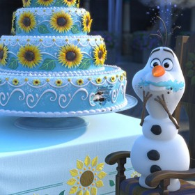 still from the animated short Frozen Fever featuring Olaf the Snowman beside a huge blue cake