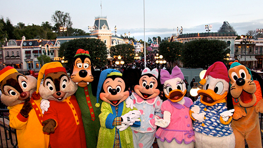 group photo of seven Disney cast member characters Chip, Dale, Goofy, Mickey Mouse, Minnie Mouse, Daisy Duck, Donald Duck, and Pluto all lined up with Disneyland Main Street behind