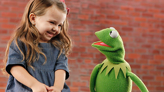 photo of little girl laughing at Kermit the Frog