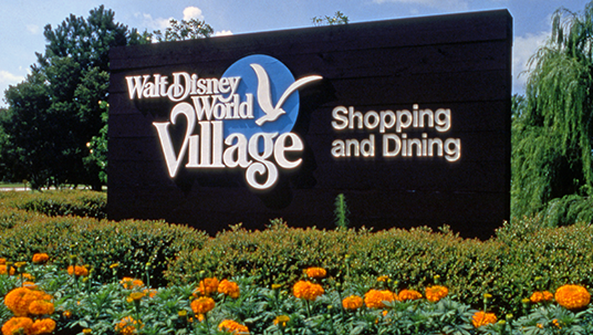 photo of large entrance sign with text Walt Disney World Village Shopping and Dining