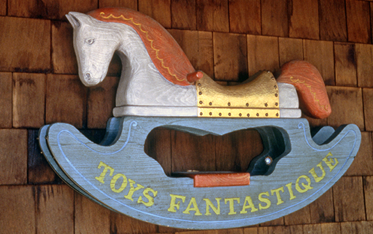 photo of fanciful carved wooden sign in the shape of a rocking horse with painted text Toys Fantastique