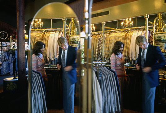 photo of sales agent assisting buyer trying on jacket reflected in full-size image