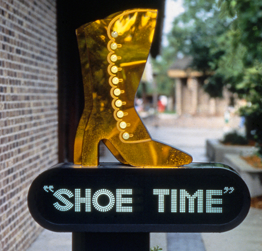 photo of sign for Shoe Time shop featuring golden women's high-heeled boot