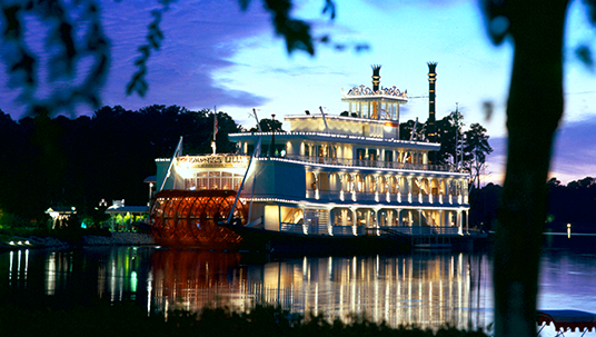 sunset photo of glamorous brightly lit riverboat with lights reflected across the lake