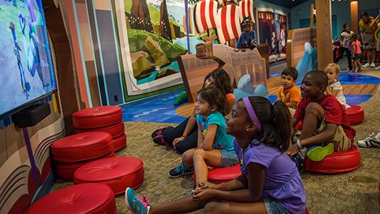 photo of children sitting on floor in playroom watching large-screen TV at Disney's Polynesian Village Resort