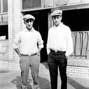 black and white photo of Roy and Walt Disney wearing caps standing in front of empty storefront