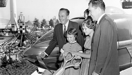 photo of Walt Disney with Vice President Richard Nixon, his wife Pat, and daughters Julie and Tricia in Disneyland attempting to cut the ribbon to celebrate the debut of the Disneyland-Alweg Monorail System, Matterhorn Bobsleds, and Submarine Voyage
