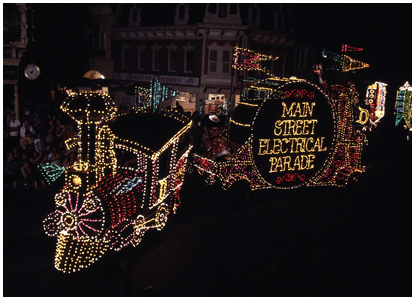 night photo of illuminated train and floats in Main Street Electrical Parade