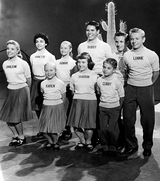 photo of nine original Mouseketeers standing in two rows bending knees in a dance step with a cactus behind them