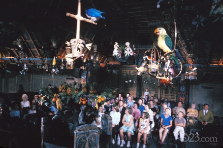 photo of enchanted children and parents seated in interior of the enchanted tiki room looking up at perched birds
