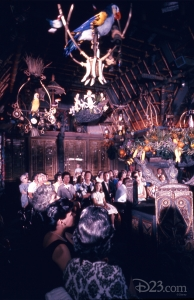 photo of well-dressed guests seated in interior of the enchanted tiki room looking up at perched birds