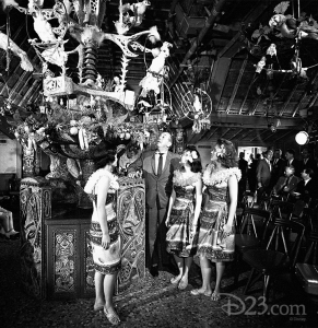 black and white photo of Walt Disney with three tropically dressed ladies inside the enchanted tiki room looking up at the central hanging display