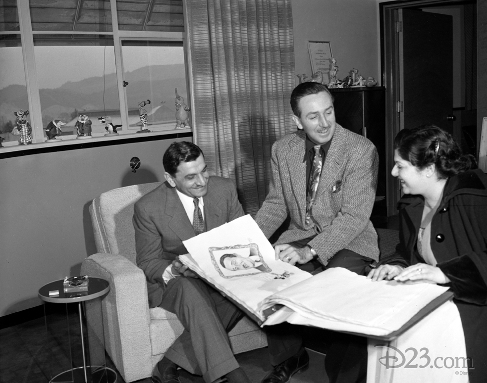 This December 1948 photo shows Walt at ease in his formal office entertaining Indian film exhibitors Kebi and Ellen Modi. Walt can be seen showcasing the scrapbook containing gifts of art from more than 50 South American artists he received in 1941.