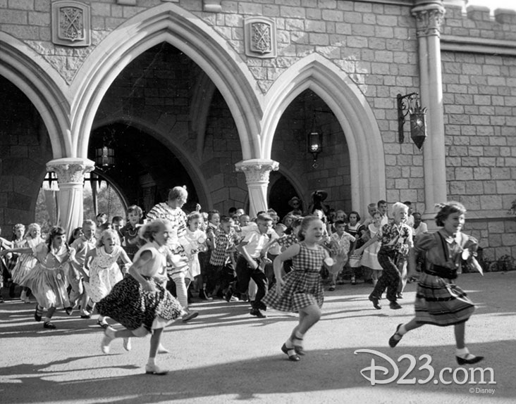 children running toward the Sleeping Beauty Castle