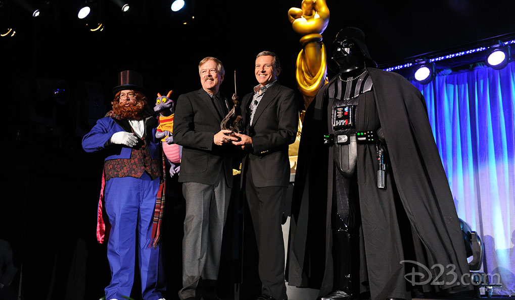 Tony Baxter and Figment receiving a Disney Legend Award from Bob Iger