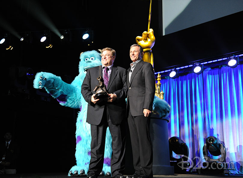 "John Goodman and James P. ""Sulley"" Sullivan receiving a Disney Legend Award from Bob Iger"