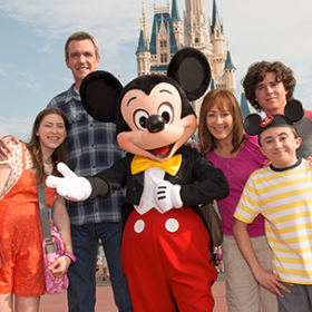 Family standing with Mickey Mouse