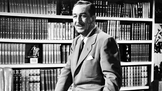photo of Walt Disney seated in library